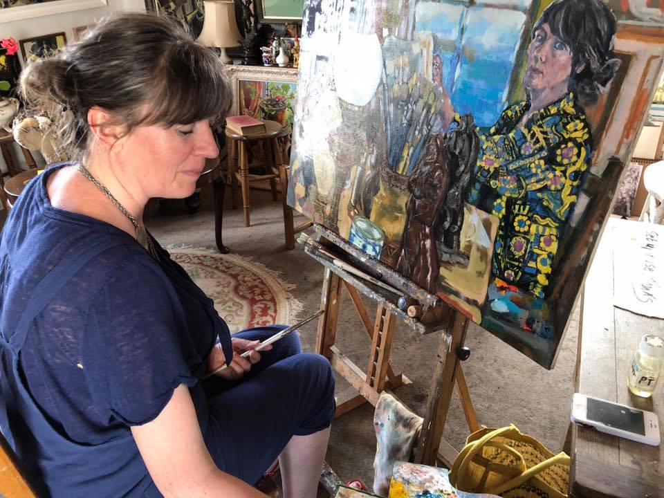 photograph showing artist Nina Packer sat at an easel painting, the picture is a large figurative portrait of an artist at work in a busy artists studio. The studio is above The New Gallery, Portscatho, Cornwall.