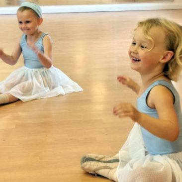 Two young children sitting and clapping during ballet class