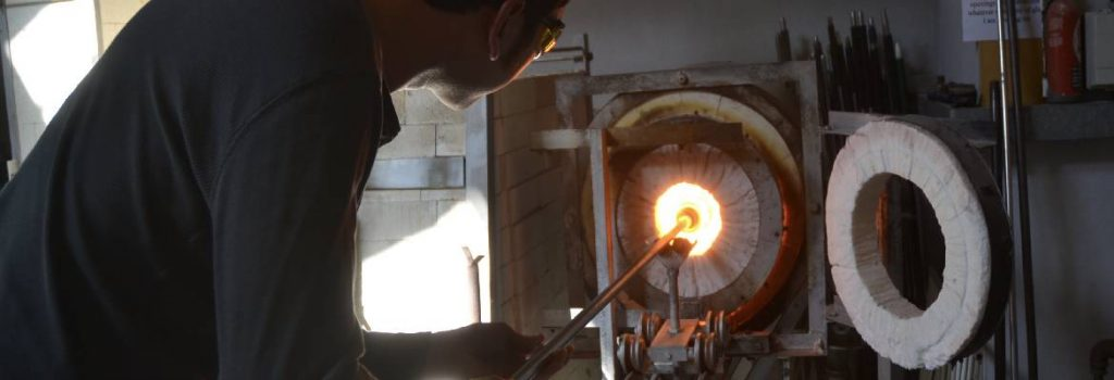 Siddy Langley Glass student reheating their piece at the gloryhole
